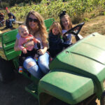 USB employee and family on farm vehicle