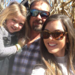 USB employee and family in front of corn stalks