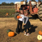USB employee's children picking pumpkins in front of a tractor