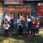 USB employees and children posing with their pumpkins in front of a barn with vintage signage hanging on it